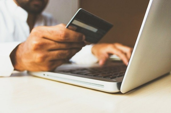 Pessoa consulta cartão de crédito para fazer compra online