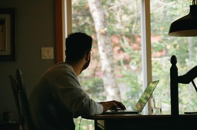 homem sentado de frente para o notebook trababalhando em home office