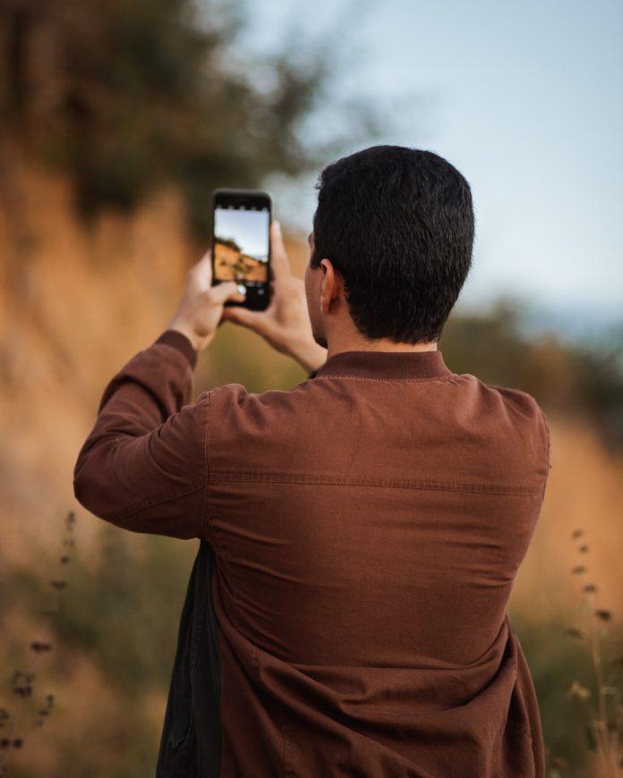 homem tirando foto de paisagem com celular