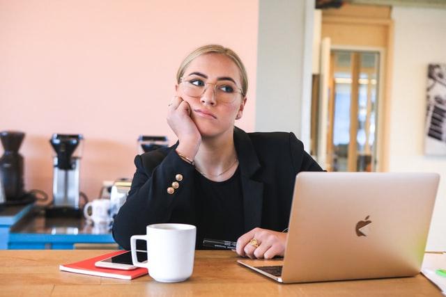 mulher sentada trabalhando em home office com notebook aberto
