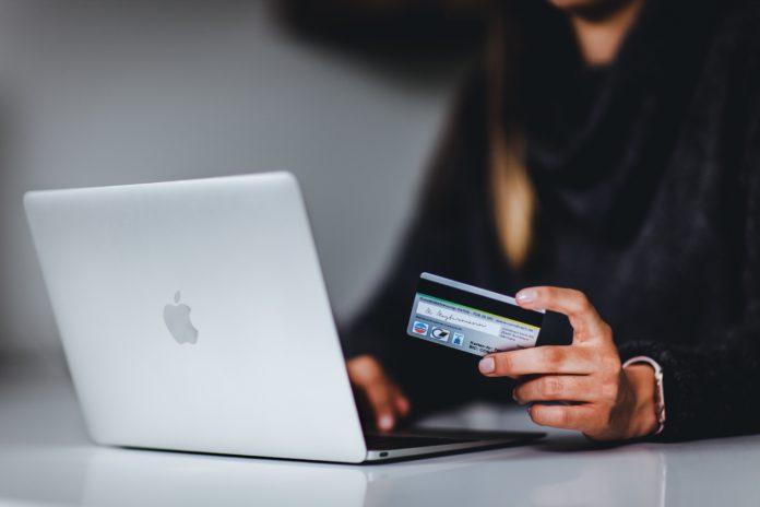 mulher usando o notebook e cartão de crédito