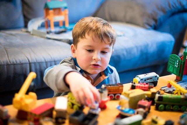 Criança brinca com carrinhos e itens de madeira