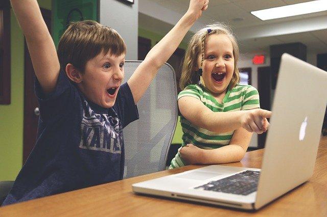 Crianças abrem os braços para comemorar uma venda feita no computador